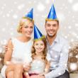Happy family in hats celebrating — Stock Photo #35897501