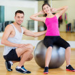 Male trainer with woman doing crunches on the ball — Stock Photo #35897939