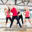 Group of smiling women stretching in the gym — Stock Photo