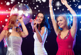 Three smiling women dancing in the club — Stockfoto