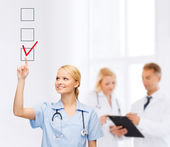 Doctor or nurse drawning checkmark into checkbox — Stock Photo