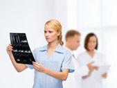 Serious doctor or nurse looking at x-ray — Stock Photo