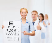 Smiling female doctor or nurse with eye chart — Stock fotografie