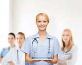 Smiling female doctor or nurse with tablet pc — Stockfoto