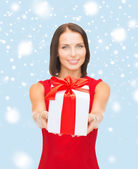 Smiling woman in red dress holding gift box — Stock Photo