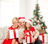 Smiling family holding gift boxes and sparkles — Stock fotografie