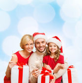 Smiling family holding gift boxes and sparkles — Φωτογραφία Αρχείου