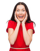 Amazed laughing young woman in red dress — Stock fotografie