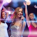Three smiling women dancing and singing karaoke — Stock Photo #35939605