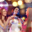 Three smiling women with cocktails and disco ball — Stock Photo #35939945