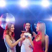 Tres mujeres sonrientes con cócteles y bola de discoteca — Foto de Stock