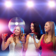 Three smiling women with cocktails and disco ball — Stock Photo #35940039