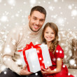 Smiling father and daughter holding gift box — Stock Photo #35941263