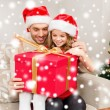 Smiling father and daughter opening gift box — Stock Photo #35941377