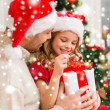 Smiling father and daughter opening gift box — Stock Photo #35941397
