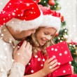Smiling father and daughter opening gift box — Stock Photo #35941443