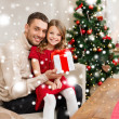 Smiling father and daughter holding gift box — Stock Photo #35941451