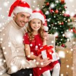 Smiling father and daughter holding gift box — Stock Photo #35941477