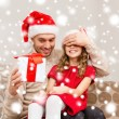 Smiling father surprises daughter with gift box — Stock Photo #35941491