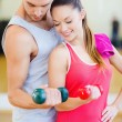 Two smiling people working out with dumbbells — Stock Photo #35942685