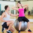 Male trainer with woman doing crunches on the ball — Stock Photo