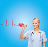 Smiling doctor or nurse drawing cardiogram — Stockfoto