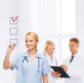 Doctor or nurse drawing checkmark into checkbox — Stock Photo