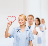 Smiling doctor or nurse drawing red heart — Stok fotoğraf