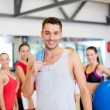Smiling man standing in front of the group in gym — Stockfoto