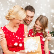 Happy family opening gift box — Stok fotoğraf