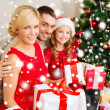 Smiling family holding many gift boxes — Stock Photo #36064165