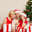 Smiling family holding gift boxes and sparkles — Stock Photo #36064377