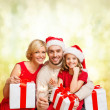Smiling family holding gift boxes and sparkles — Stock Photo #36064427