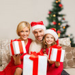 Smiling family giving many gift boxes — Stock Photo