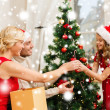 Smiling family decorating christmas tree — Stock Photo #36064621