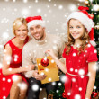 Smiling family decorating christmas tree — Zdjęcie stockowe #36065415