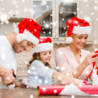 Smiling family in santa helper hats with gift box — Stock Photo