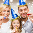 Smiling family in blue hats blowing favor horns — Stock Photo #36065783