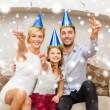 Happy family in blue hats throwing serpentine — Zdjęcie stockowe