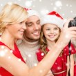 Smiling family in santa helper hats taking picture — Zdjęcie stockowe