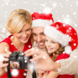 Smiling family in santa helper hats taking picture — Stock Photo