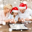 Happy family in santa helper hats making cookies — Stock Photo