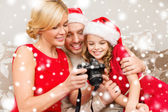 Family in santa helper hats looking at pictires — Stock Photo