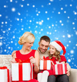 Happy family opening gift boxes — Stock Photo