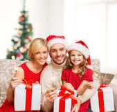 Smiling family holding gift boxes and sparkles — Photo