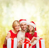 Smiling family holding gift boxes and sparkles — Zdjęcie stockowe