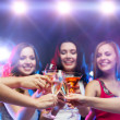 Three smiling women with cocktails and disco ball — Stock Photo #36115087