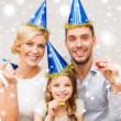 Smiling family in blue hats blowing favor horns — Stockfoto