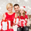Smiling family holding many gift boxes — Stock Photo #36115731