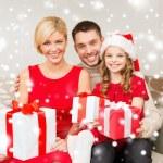 Smiling family holding many gift boxes — Stock Photo